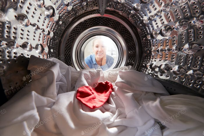 Woman Looking Inside Washing Machine With Red Sock Mixed With White Laundry