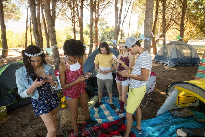 Friends using mobile phones while standing at campsite