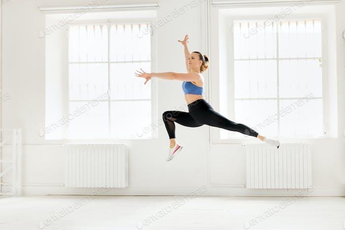Woman performing an enjambe acro gymnastic jump
