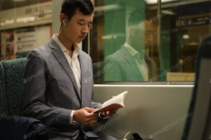 Young Asian businessman in wireless earphones intently reading book in subway train alone