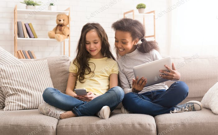 Preteen girls with gadgets sitting on sofa at home