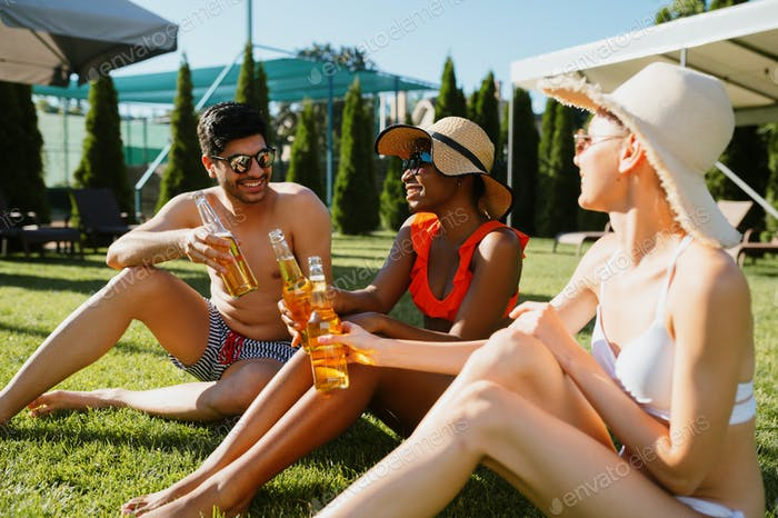 Cheerful friends drink beer near the pool