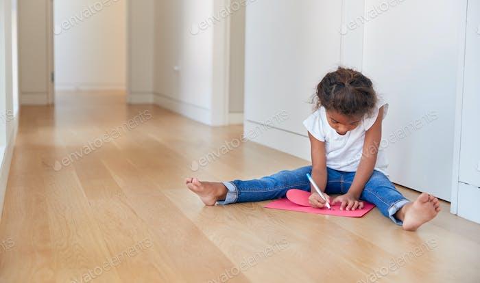 Hispanic Girl Sitting On Floor Making Card For Mothers Day