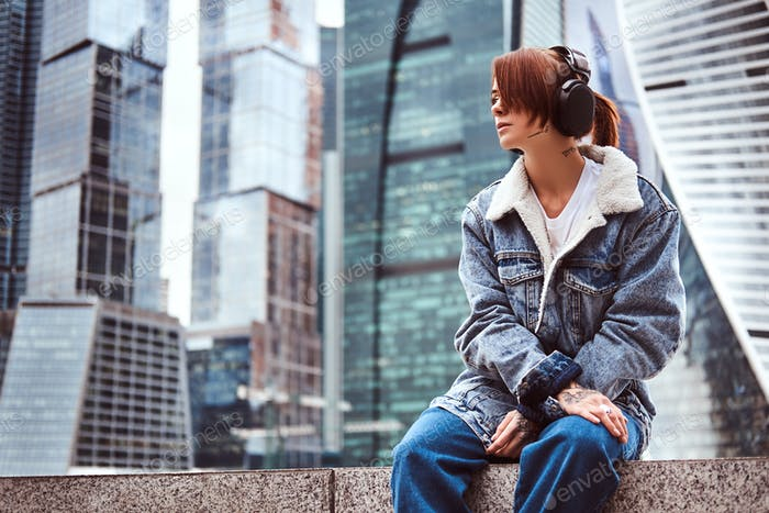 Trendy dressed redhead girl in front of skyscrapers in Moscow city