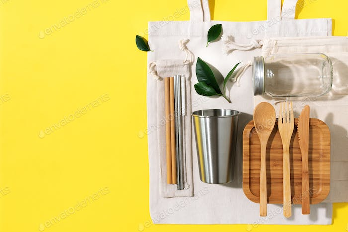 Cotton bags, glass jar, bottle, metal cup, straws for drinking, bamboo cutlery and boxes on yellow