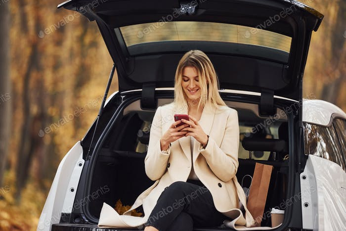 Girl sits on the back of car. Modern brand new automobile in the forest