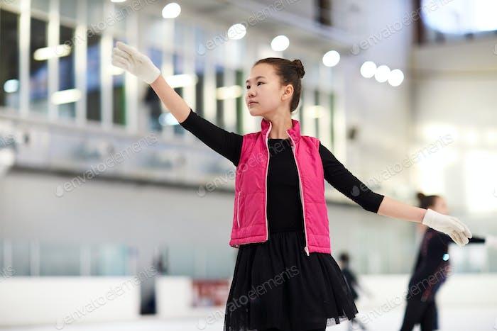 Asian Girl Figure Skating in Rink