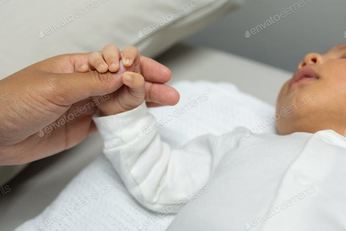 Close-up of Caucasian baby holding female doctors finger in hospital