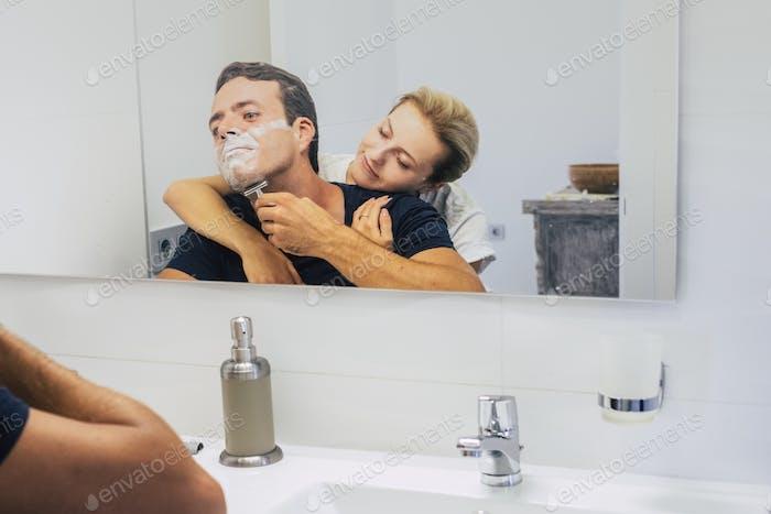 Junges Paar zu Hause im Schlafzimmer, während der Mann tut und den Bart schneidet, um den Tag zu beginnen