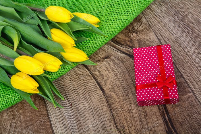 Yellow tulips and gift on a wooden table