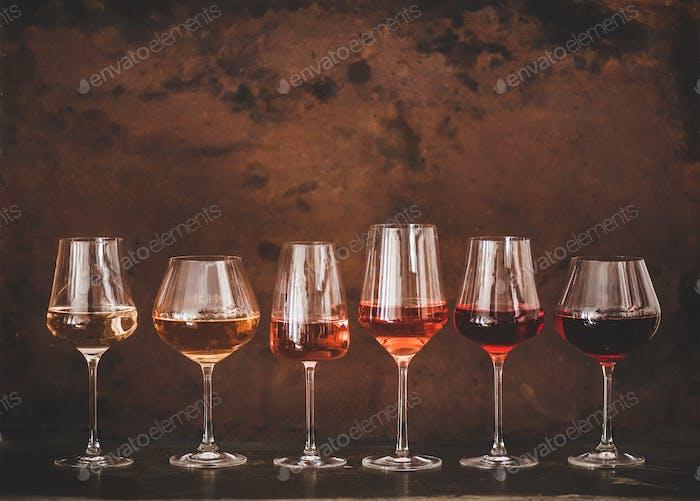 Schattierungen von Rosenwein in Gläsern, rostigen Hintergrund, Kopierraum