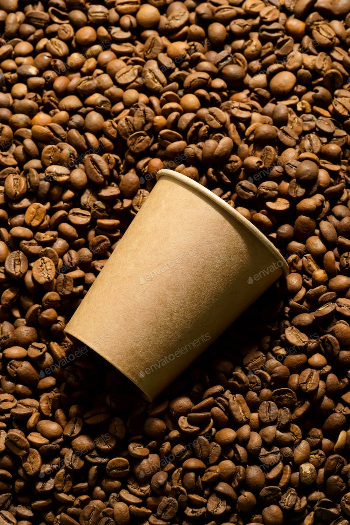 Paper mockup eco friendly cup on a pile of coffee beans
