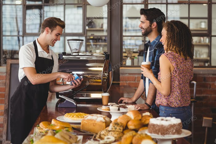 Smiling barista taking credit card from hipsters at coffee shop