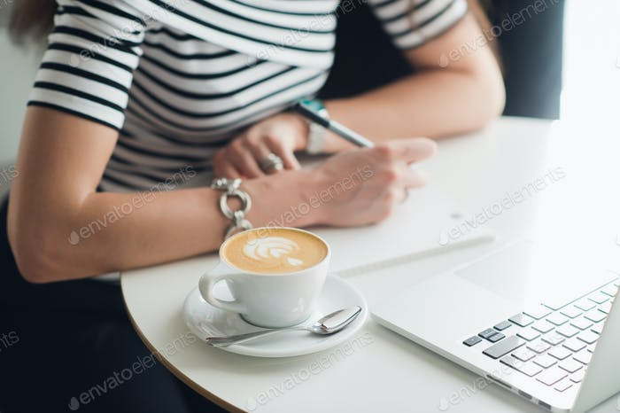 Close up picture of a cup of cappuccino with a pattern and hands writing in a notebook. Woman