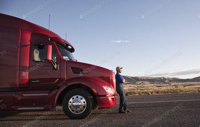 Truck driver leaning on the grill of his commercial truck.