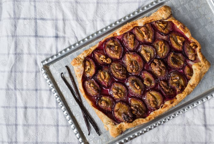 Rustic plum pie with walnuts and ice-cream