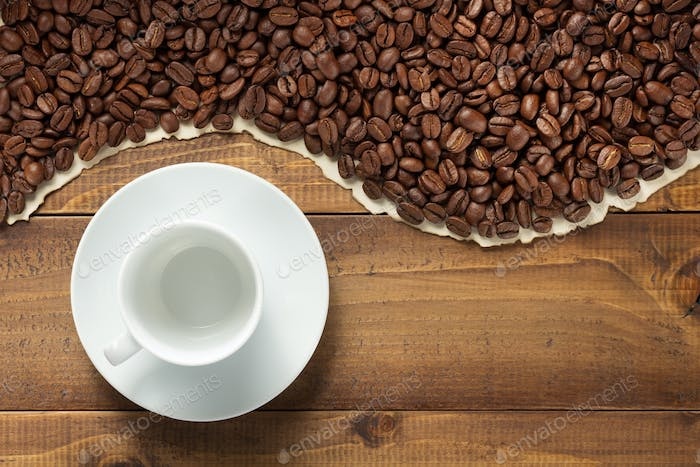 coffee beans and empty cup on wooden background