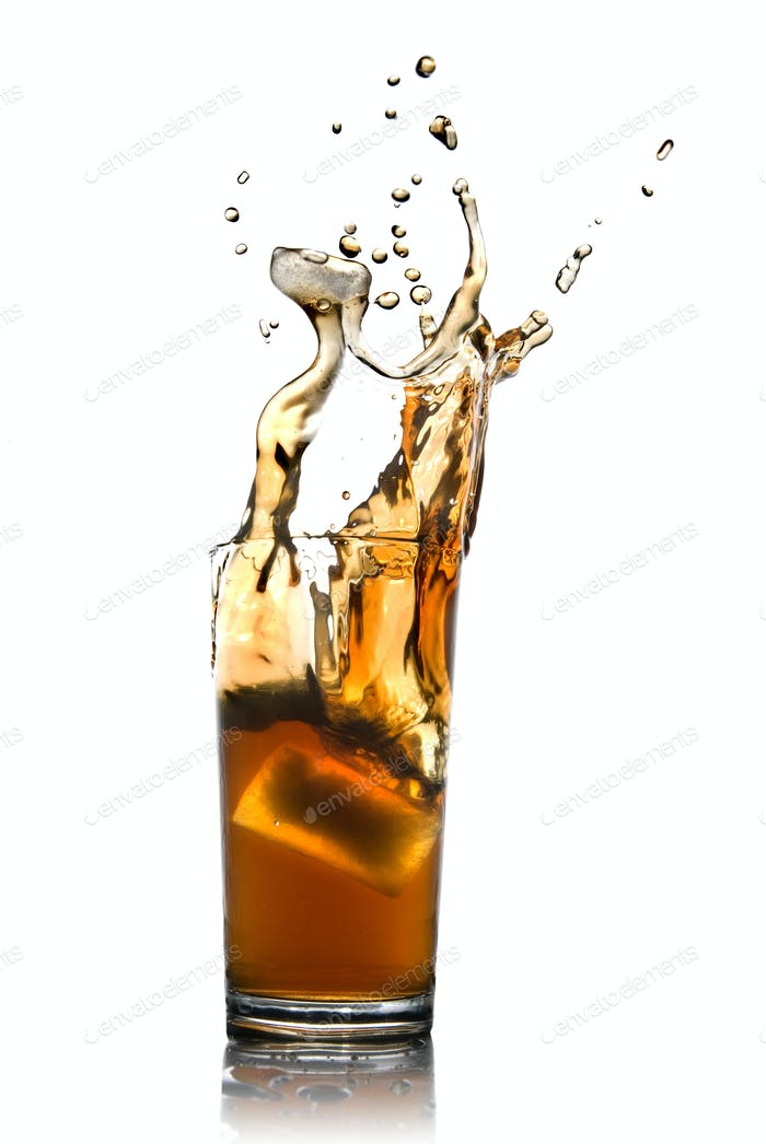Beautiful splash of cola with ice in glass isolated on white