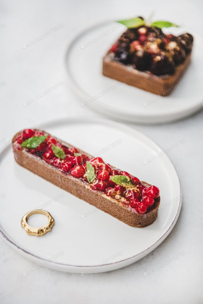 Tart with red currant and golden ring in white plate