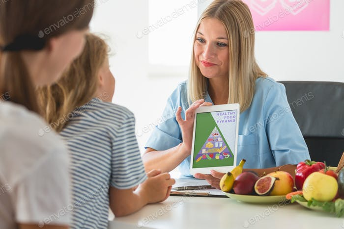 Worried mother and little boy during a visit to a dietitian preparing a healthy diet plan