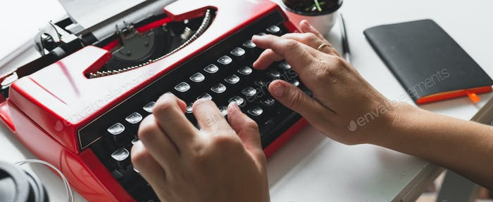 Woman hand working with bright red vintage typewriter