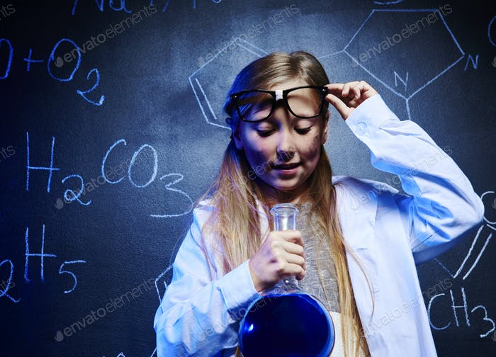 Blonde scientist looking at chemistry liquid