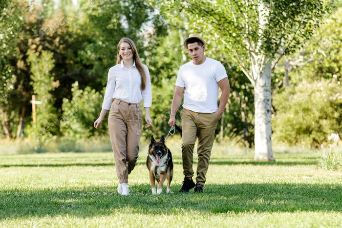 Young and modern couple walking and playing with their dog Border Collie in a park