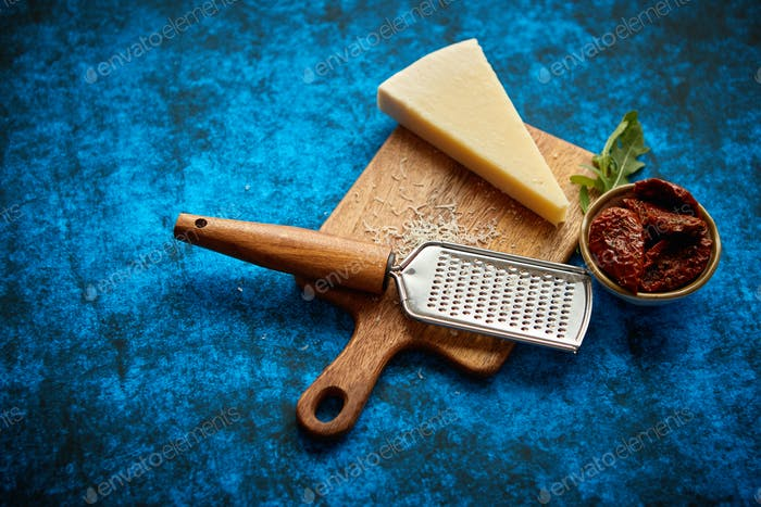 Grated parmesan cheese and metal classic grater placed on wooden cutting board
