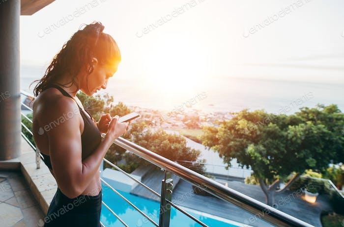 Mujer de fitness en el balcón Uso teléfono Móvil