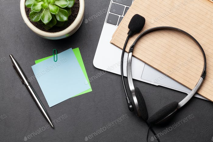 Office desk with headset and laptop