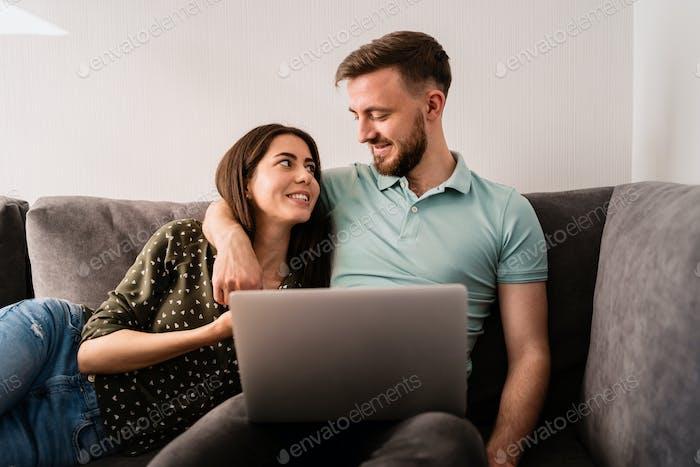 Hombre y mujer sentado en el sofá con una computadora portátil