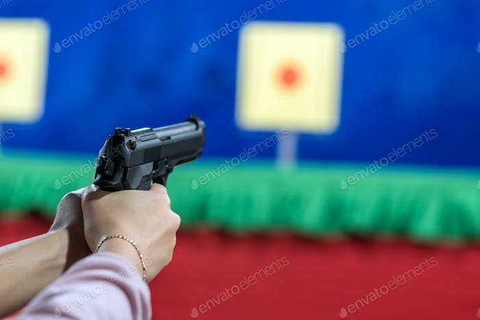 Rear view of woman with her gun on shooting at the target in practice Shooting Range,