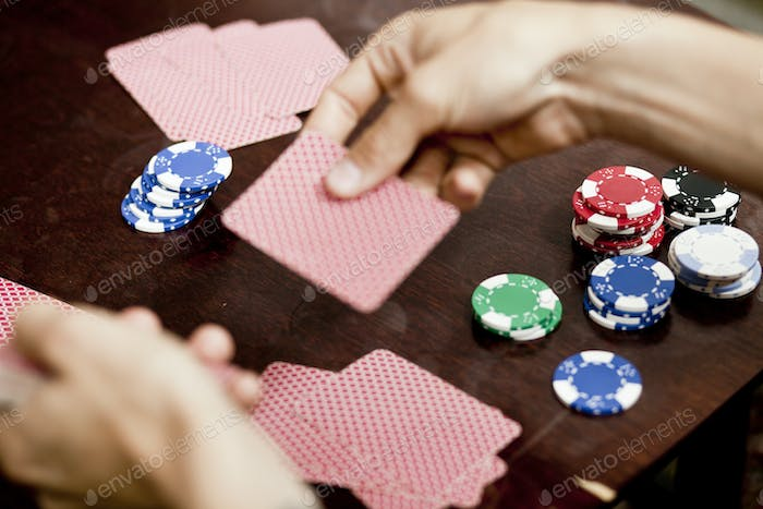 Cropped image of man's hands playing cards at home