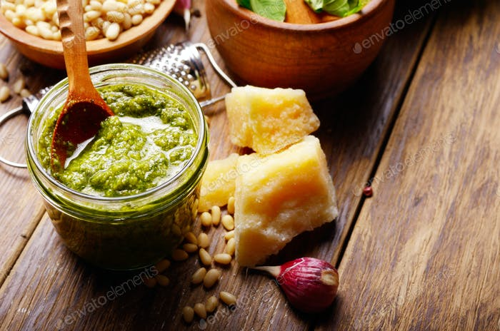 Pesto sauce ingredients and utensils on wood table