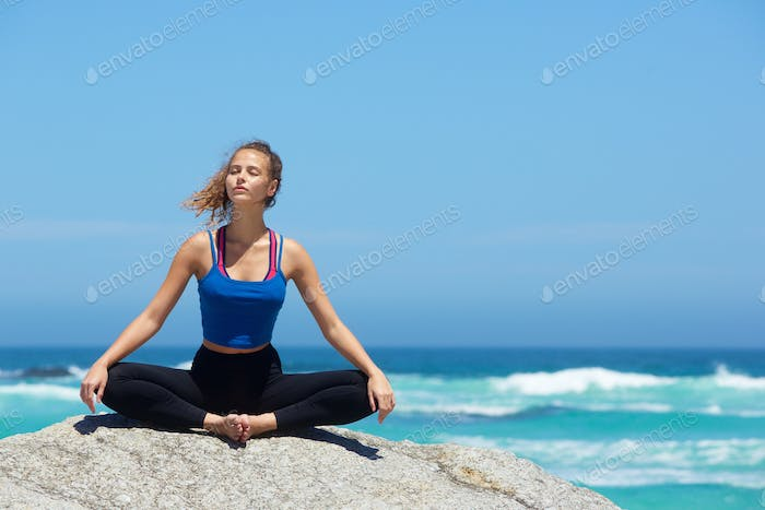 Yoga woman sitting alone by the sea