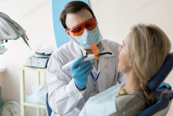 Dentist working with client in chair