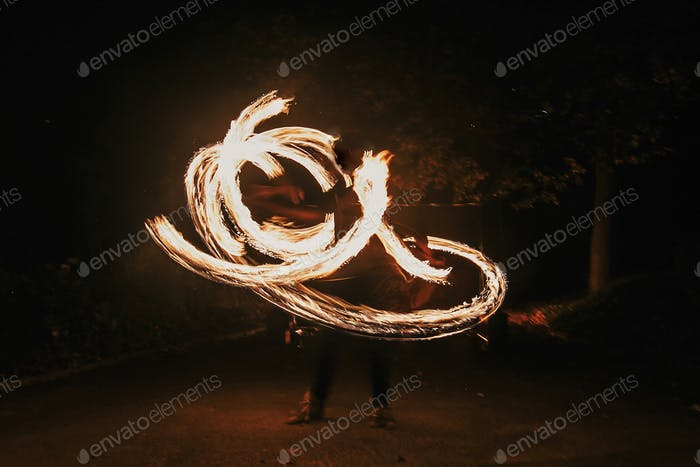 Fire dancers swing, spinning fire and man juggling with bright sparks in the night