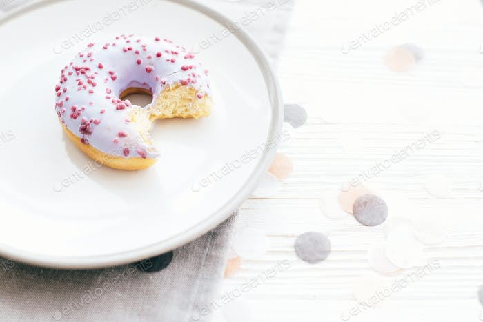 Delicious donut with sprinkles on stylish plate on white table with confetti