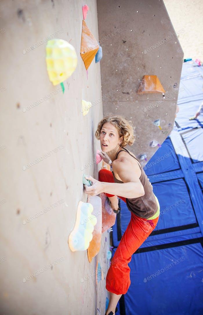Weibliche Klettererin auf künstlicher Kletterwand