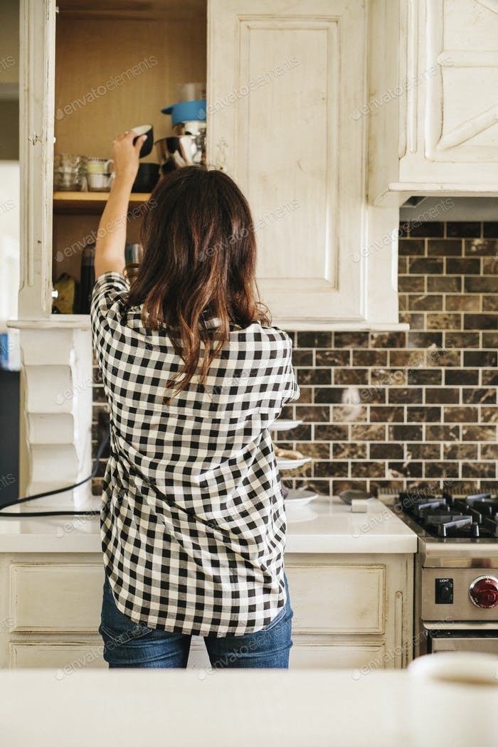 Rear view of  woman with long brown hair, wearing a chequered shirt, standing in a kitchen.