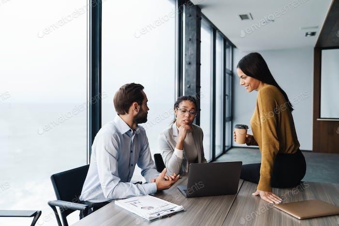 Bild von jungen weiblichen und männlichen Kollegen, die an Laptops im Büro arbeiten