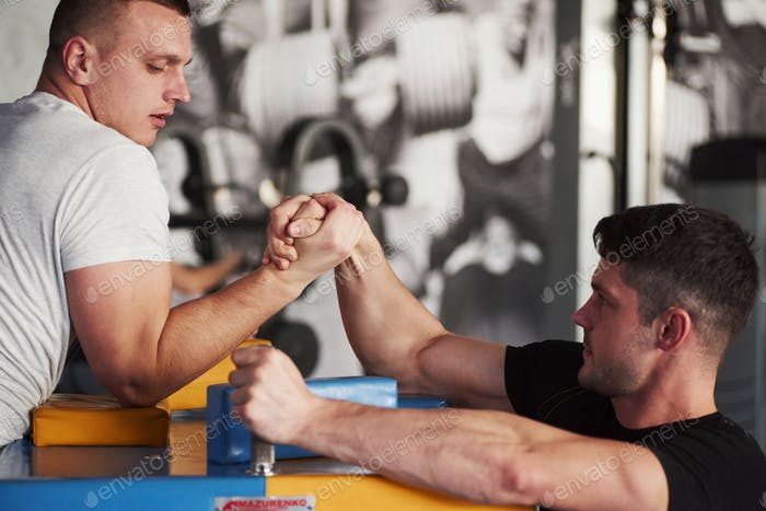 Don't surrender. Arm wrestling challenge between two men. Match on a special table