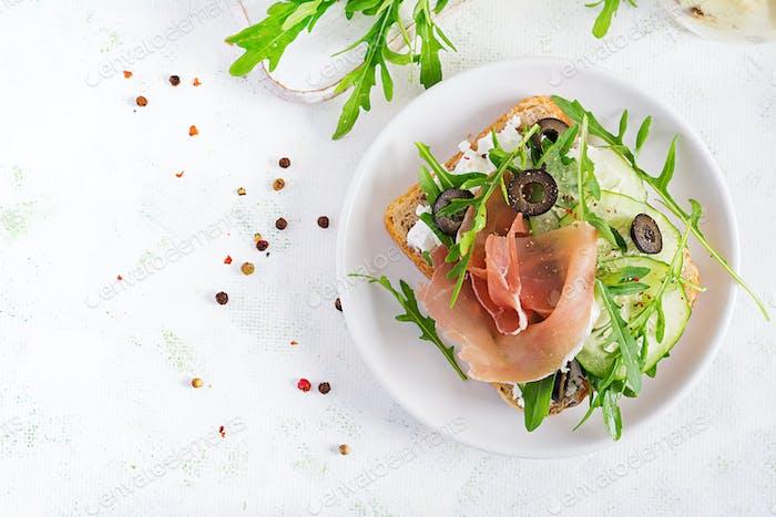 Sandwich mit Schinken, Gurken, schwarzen Oliven, Rucola und Feta-Käse