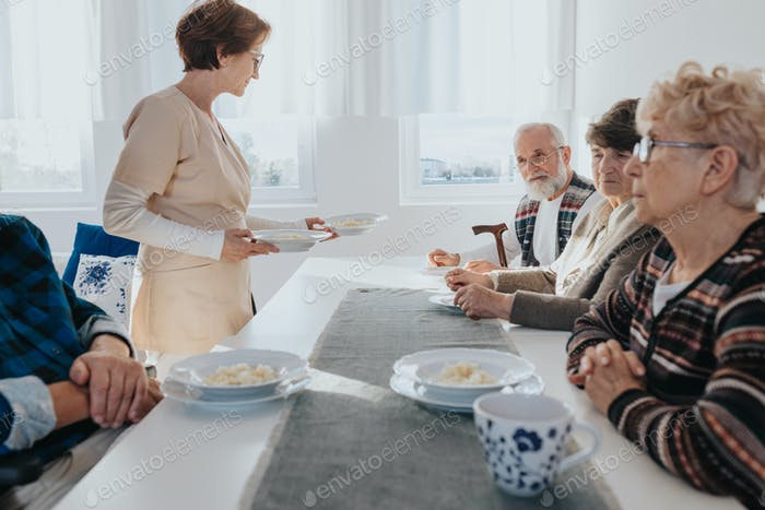 Senior patients and nurse in local nursing home during dinner time