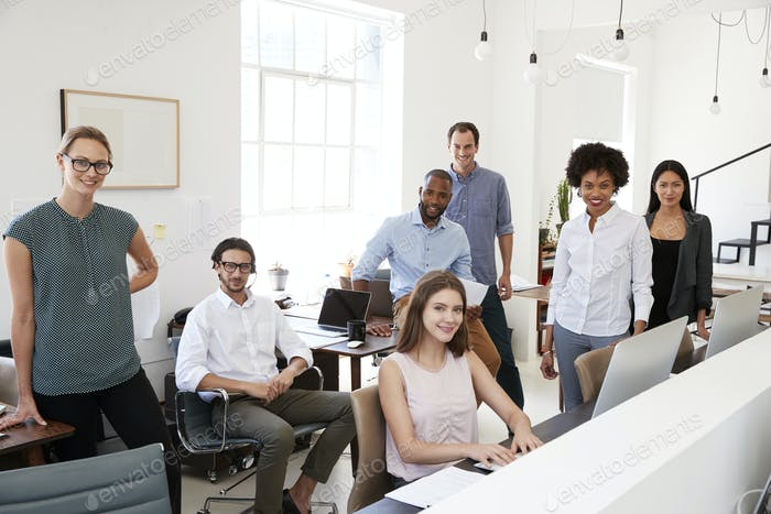 Young business colleagues smiling to camera in their office