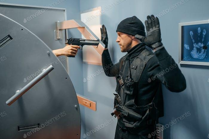 Räuber stehend an Gewölbe Tür mit den Händen hoch