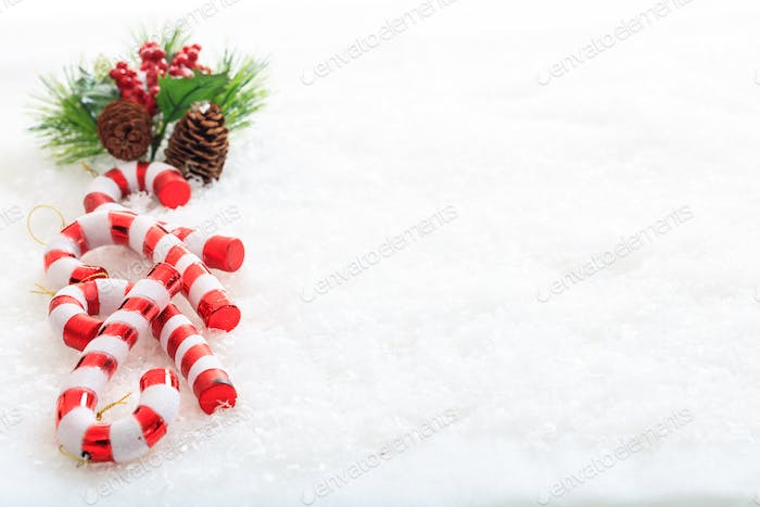 Pine cones and candy canes on snow