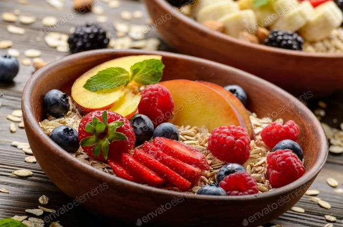 Fruit healthy muesli with peaches strawberry almonds and blackberry in clay dish