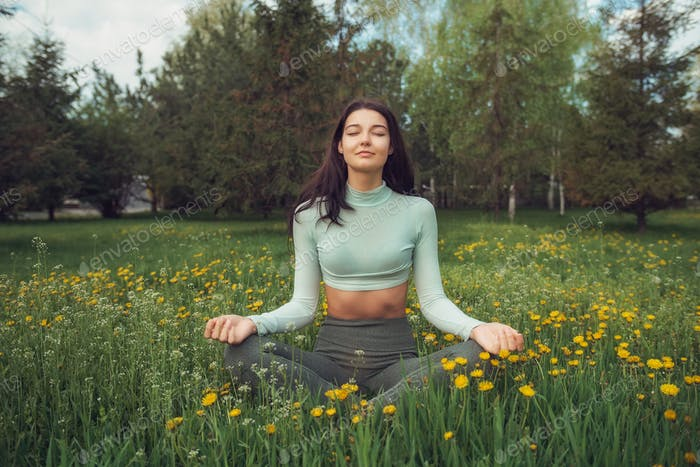 Woman Meditating on the Meadow Outdoors