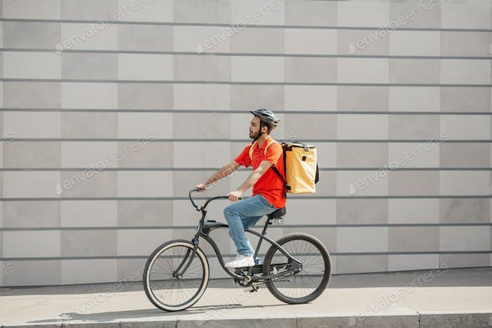 Junge kaukasische Mann Radfahrer in Schutzhelm mit Rucksack Reiten Fahrrad auf Bürgersteig mit